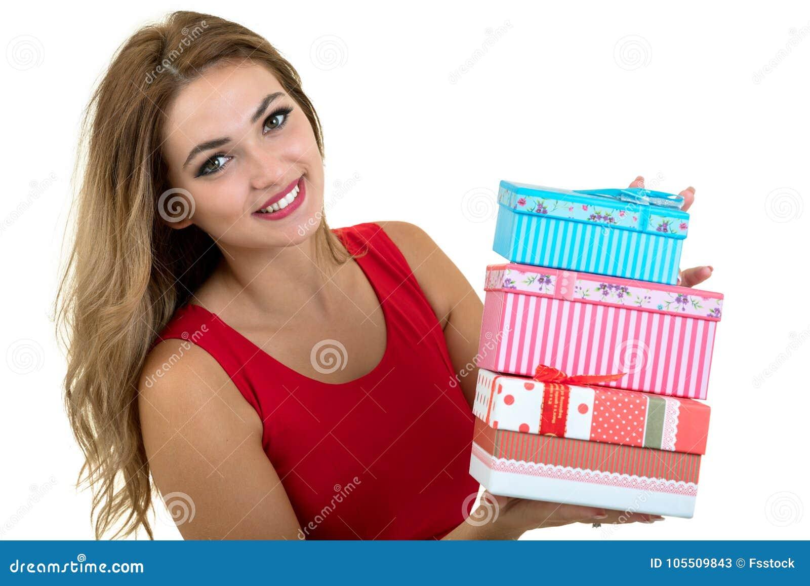 Portrait d une jolie pile de sourire de participation de fille de boîte-cadeau d isolement au-dessus du fond blanc
