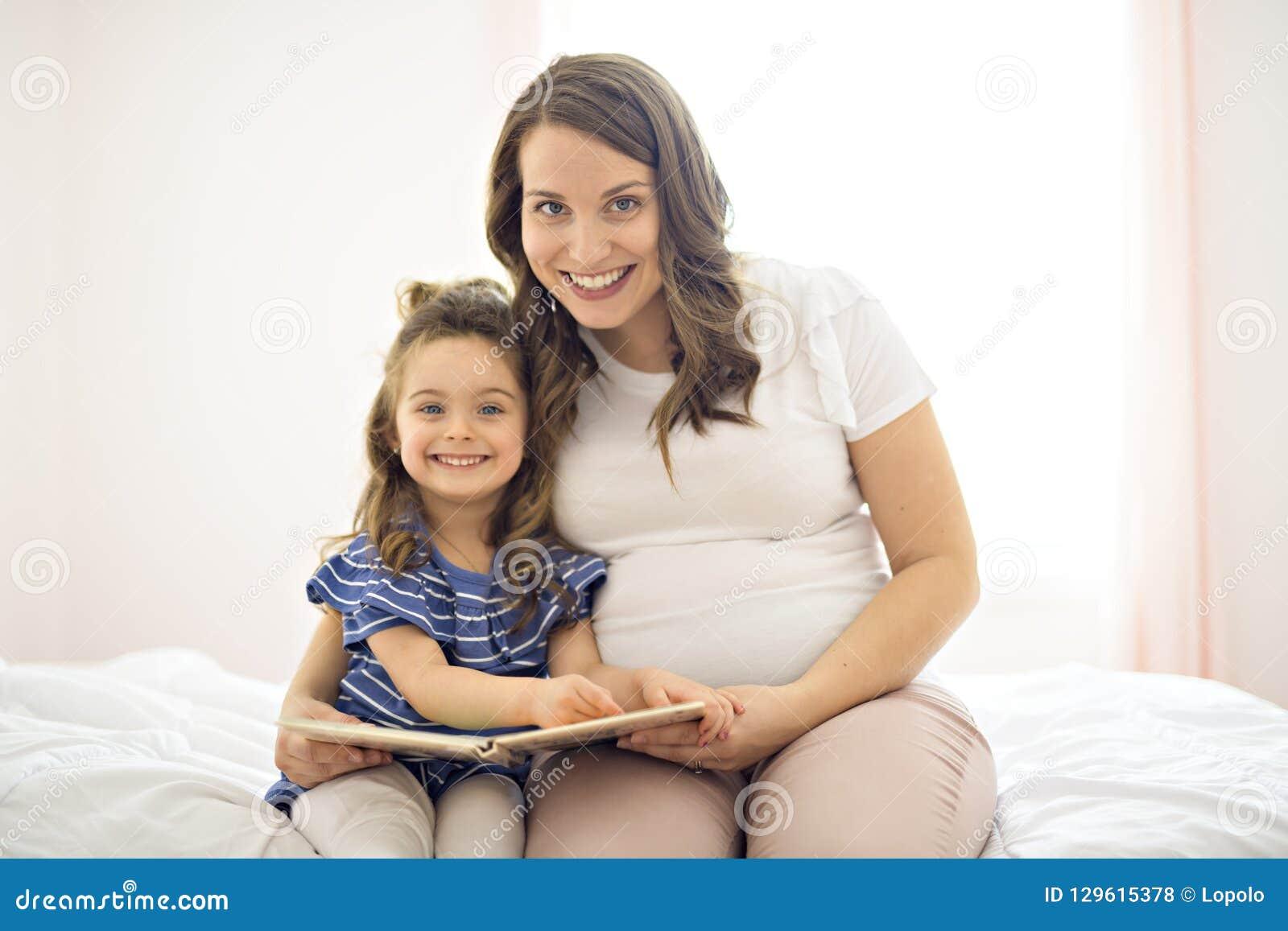 Portrait d une mère et d une fille lisant un livre se trouvant et détendre dans le lit