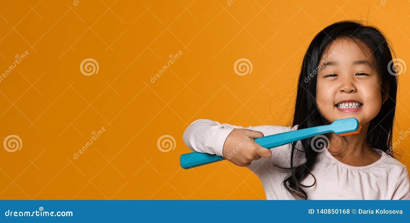 Portrait d une petite fille tenant une brosse à dents au-dessus de fond jaune
