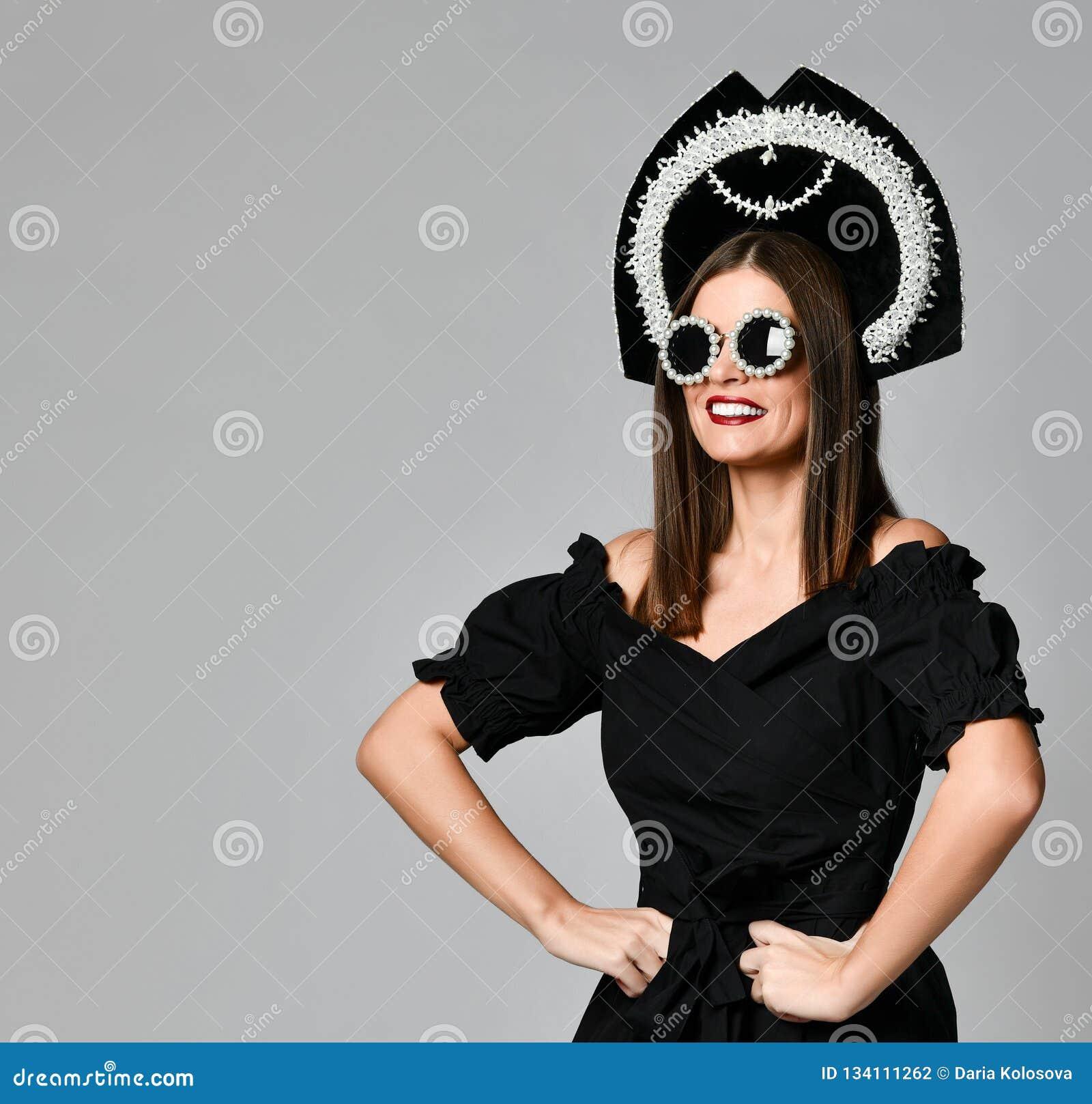 Portrait d une robe élégante de noir de brune, des lunettes de soleil noires, d un chapeau de kokoshnik, de longs cheveux et d un