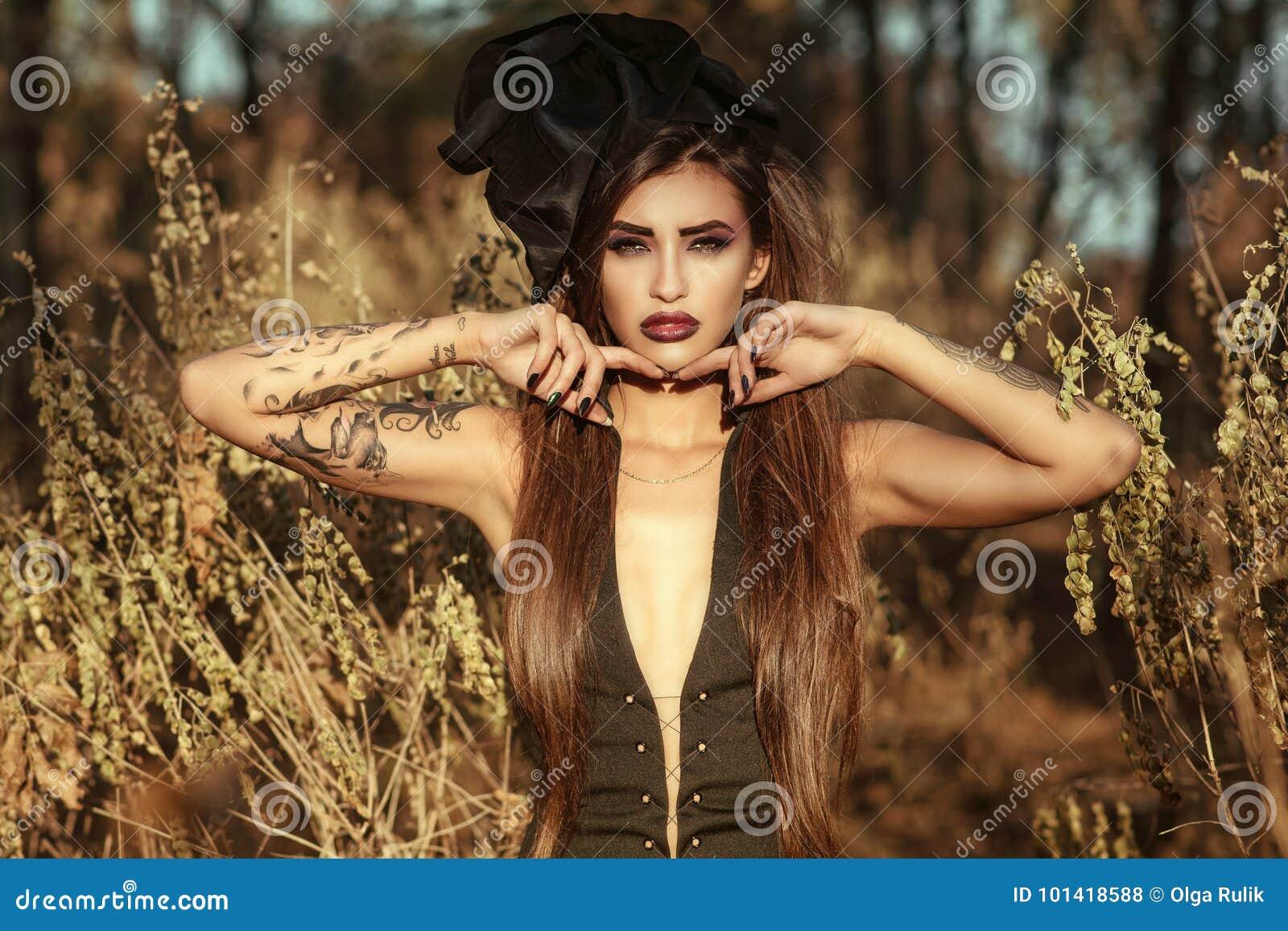 Portrait d une sorcière tatouée dangereuse snob utilisant la robe sexy de corset et le chapeau en soie de vintage se tenant dans