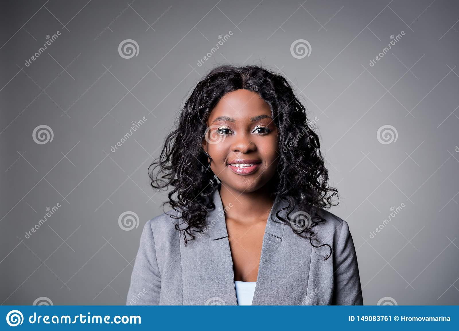 Portrait dark-skinned beautiful woman a gray jacket with dark curly hair, looking smile