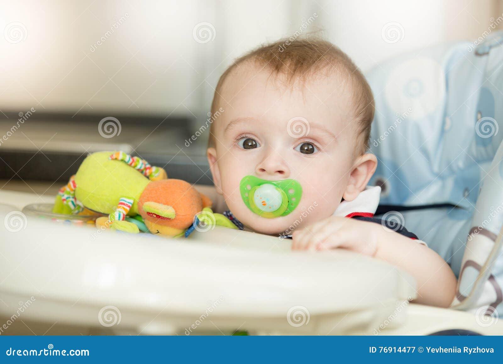 Portrait de bébé garçon mignon avec le petit déjeuner de attente de soother dedans