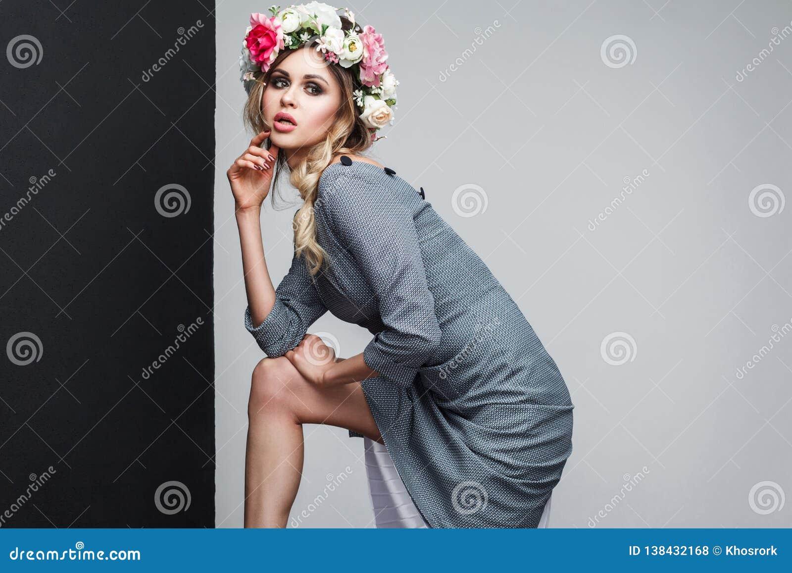 Portrait de beau mannequin sensuel en robe grise avec le maquillage et fleurs principales sur sa tête posant et regardant loin