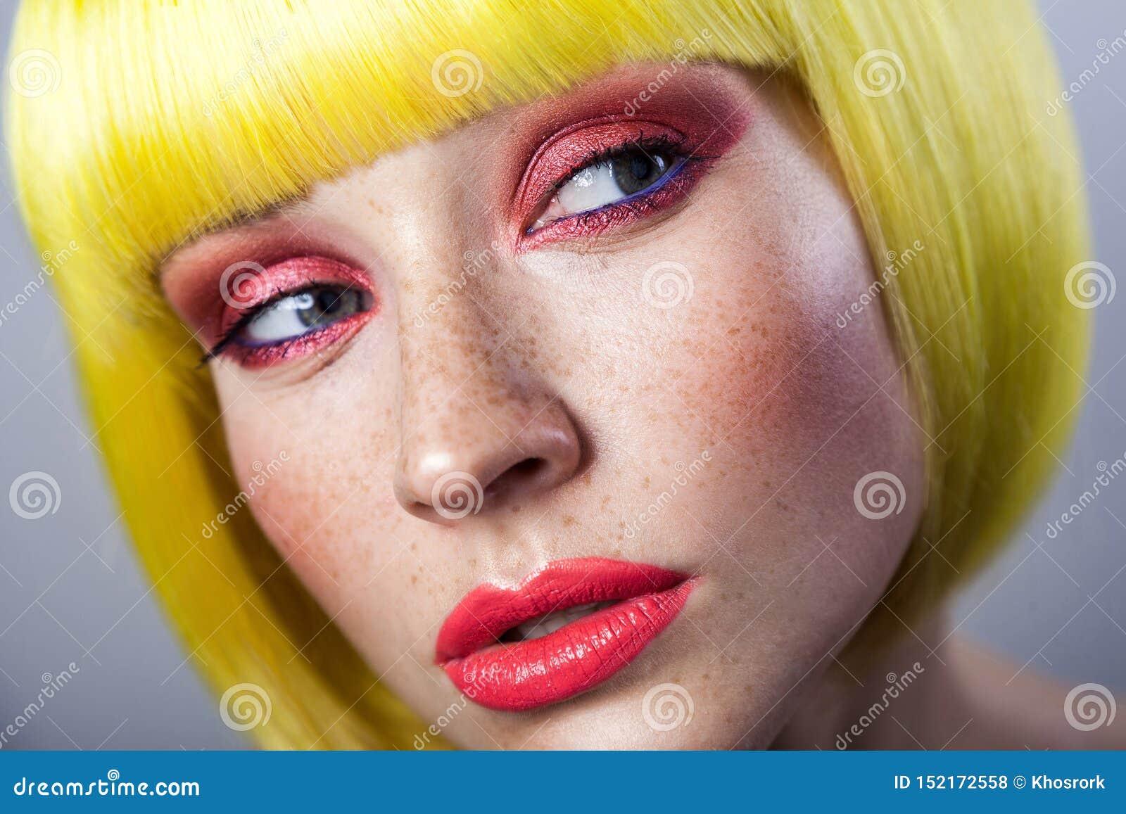 Portrait de beauté de jeune modèle femelle mignon avec des taches de rousseur, maquillage rouge et perruque jaune, regardant loin