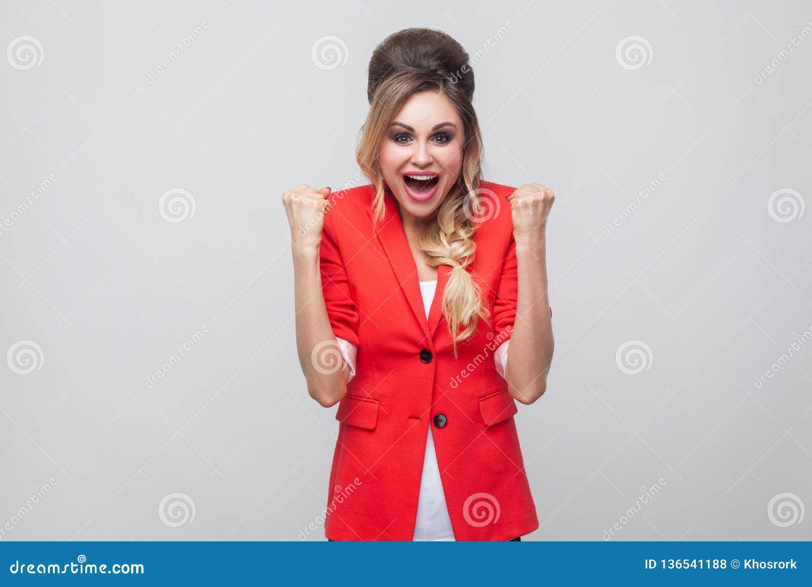 Portrait de belle dame heureuse enthousiaste d affaires avec la coiffure et le maquillage dans le blazer de fantaisie rouge, se t