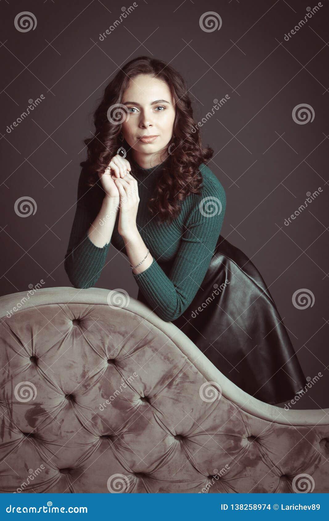 Portrait de belle femme avec le maquillage, sur un sofa, dans le chandail vert et la jupe en cuir noire posant sur le fond foncé