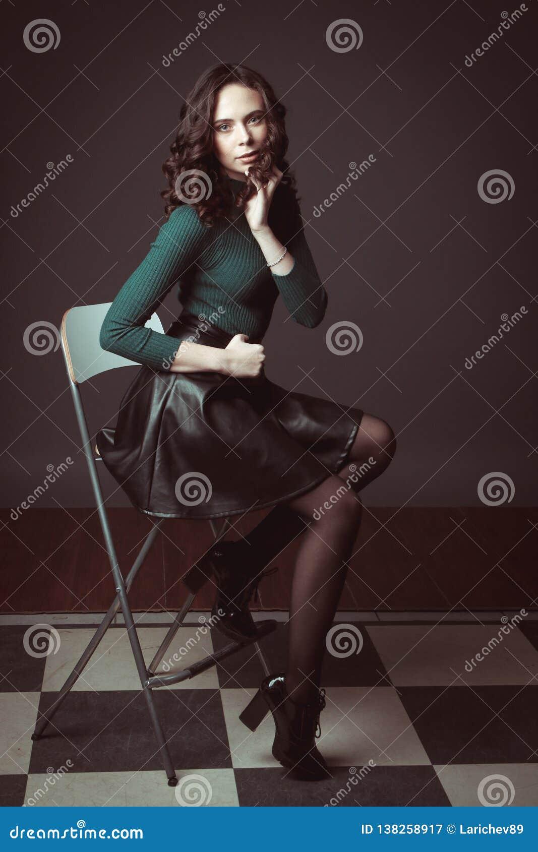 Portrait de belle femme avec le maquillage, sur une chaise, dans le chandail vert et la jupe en cuir noire posant sur le fond fon