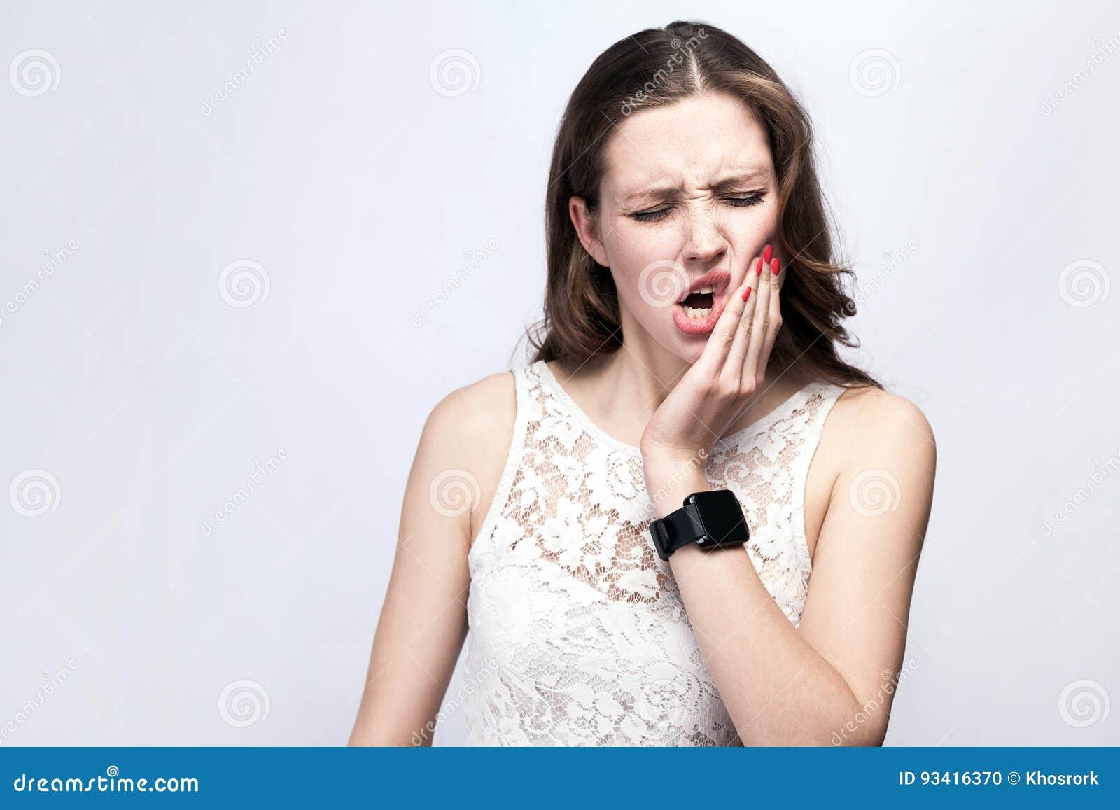 Portrait de belle femme avec les taches de rousseur et la robe de blanc et la montre intelligente avec douleur de dent sur le fon