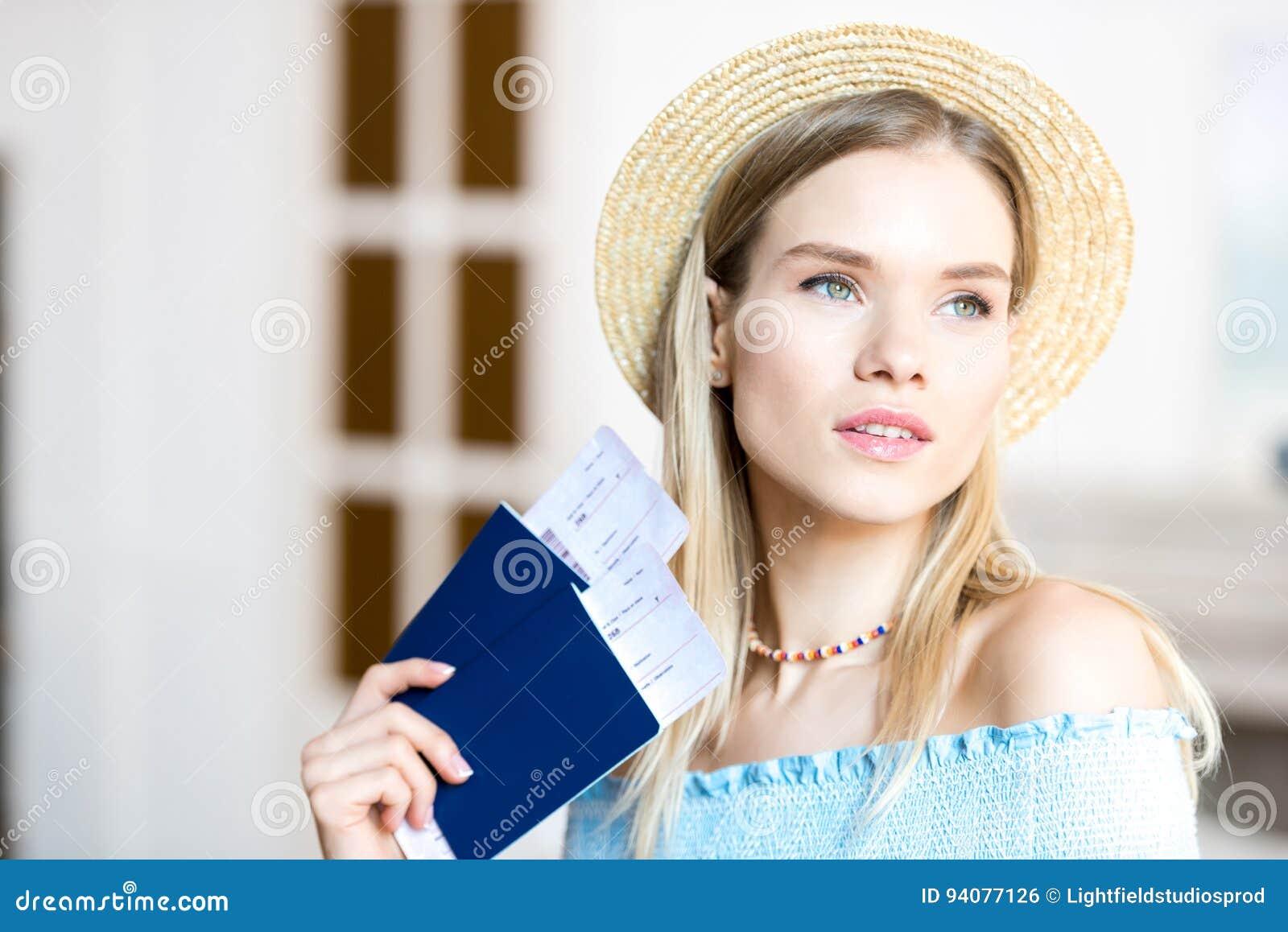 Portrait de belle jeune femme blonde dans le chapeau tenant des passeports et des billets