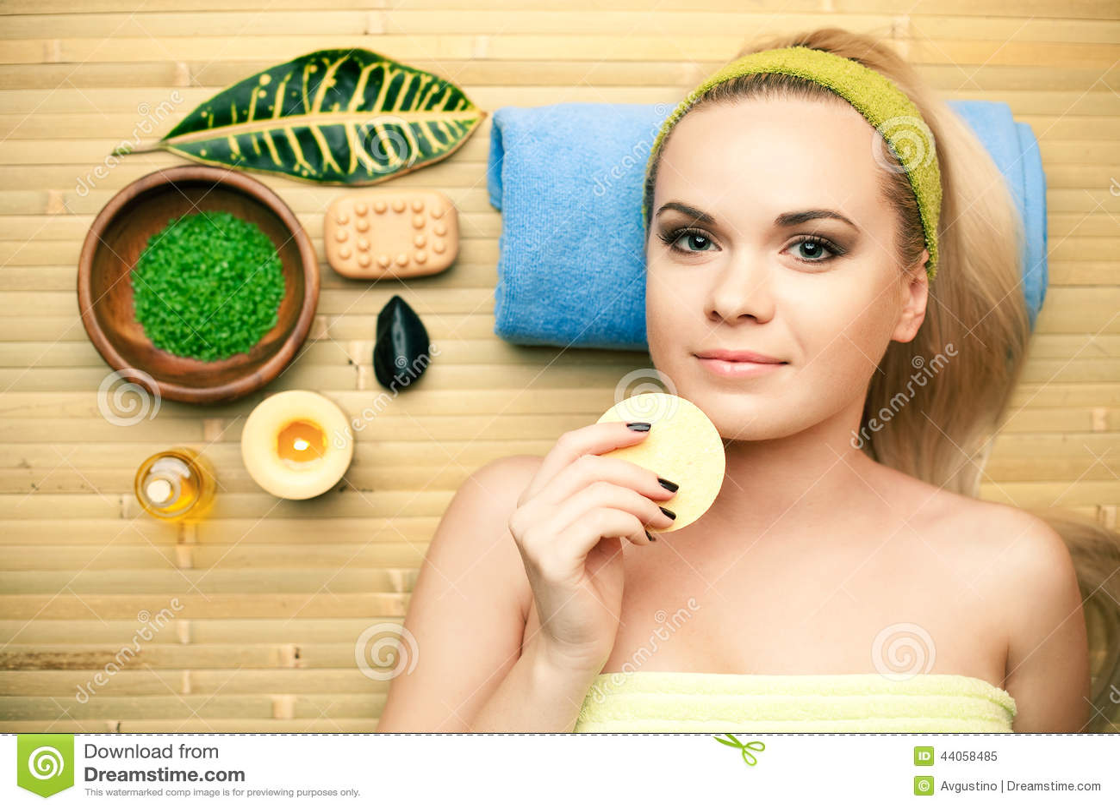 Portrait de belle jeune femme touchant son visage avec l éponge