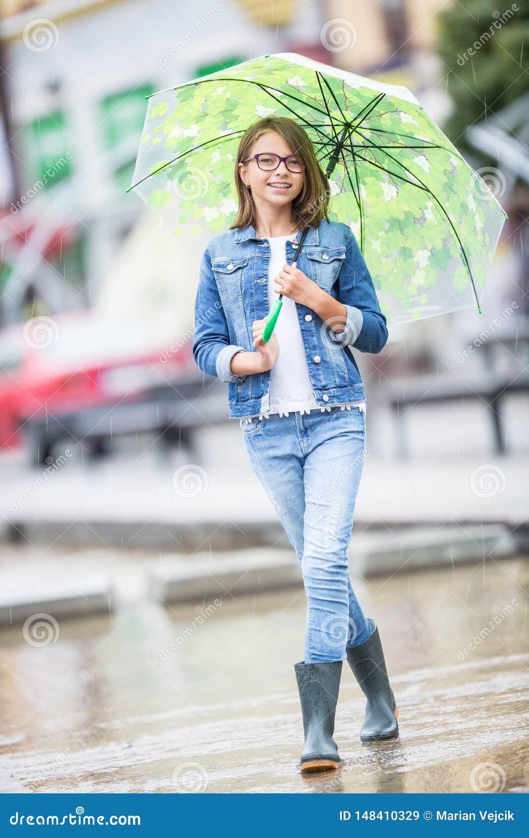 Portrait de belle jeune fille de la pr?adolescence avec le parapluie sous le ressort ou la pluie d ?t?