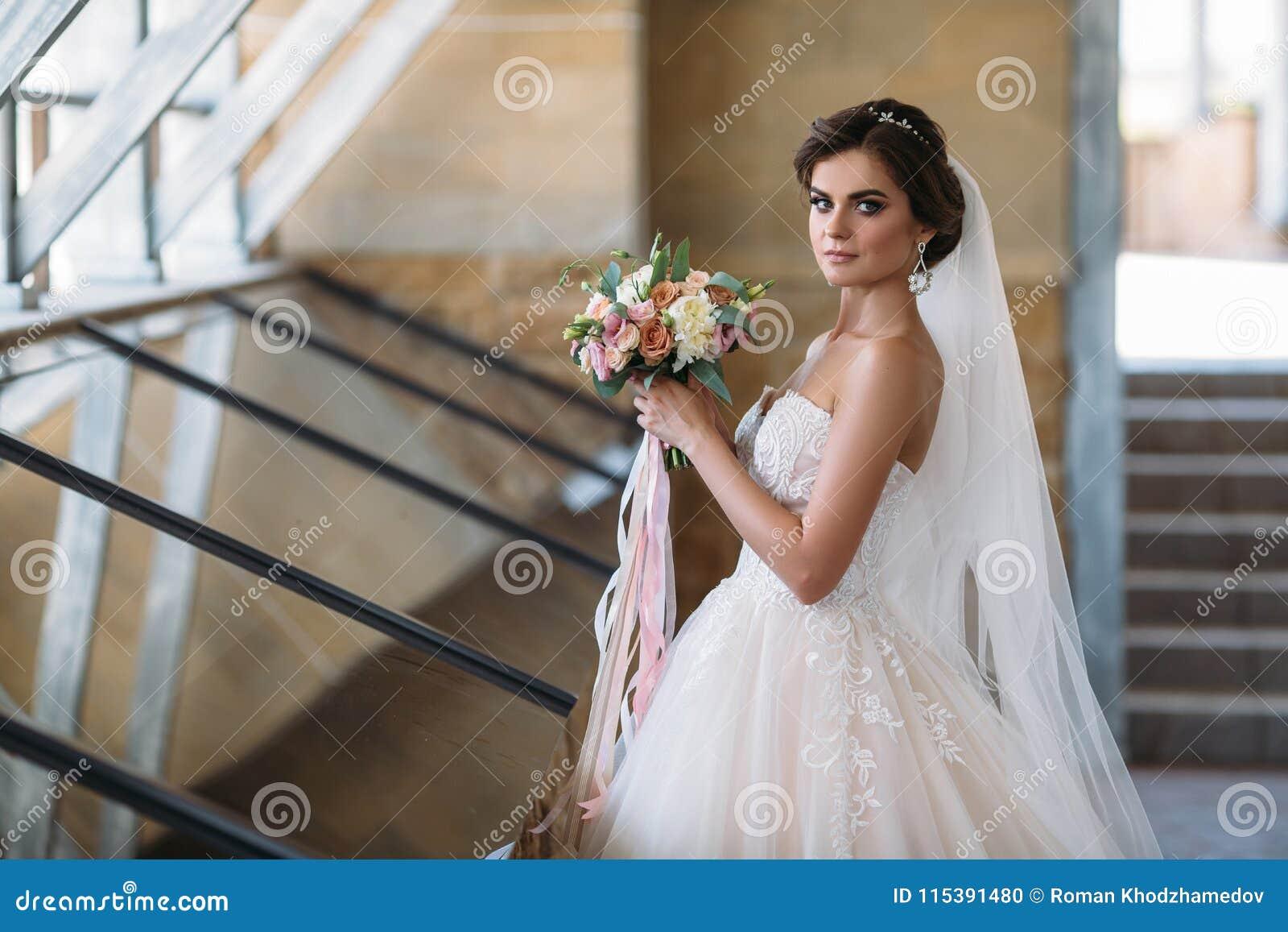 Portrait de belle jeune mariée avec des fleurs de bouquet dans la robe de luxe blanche Modèle magnifique avec le maquillage et la
