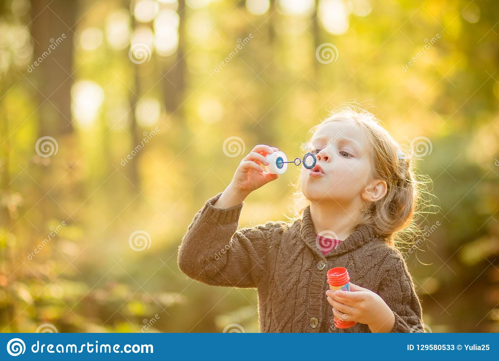 Portrait de belles bulles de savon de soufflement drôles de petite fille Fille aux yeux bleus blonde mignonne dans le manteau tri