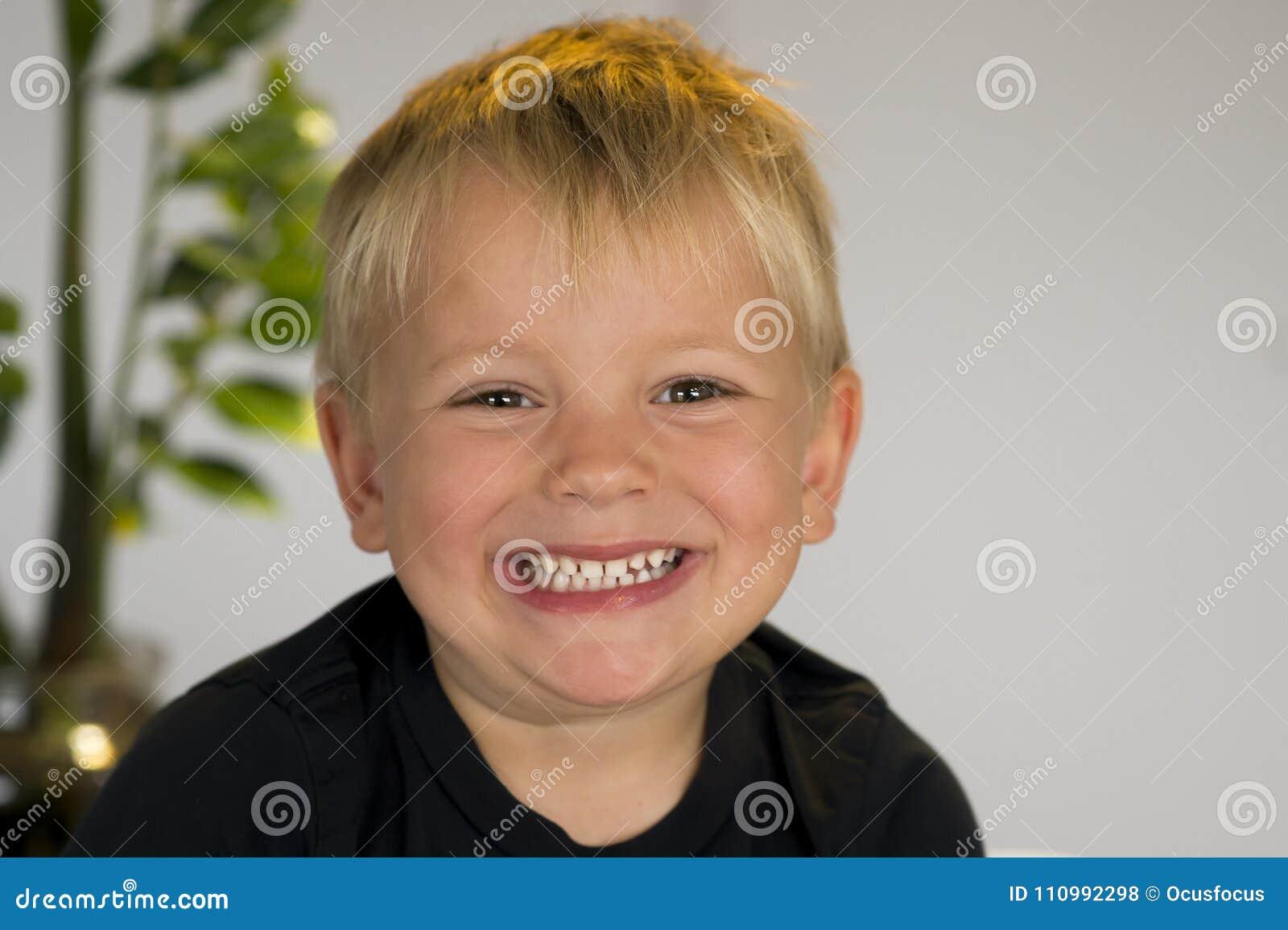 Portrait de belles 3 ou 4 années blondes de sourire caucasien d enfant heureux dans l expression joyeuse de visage à la maison re
