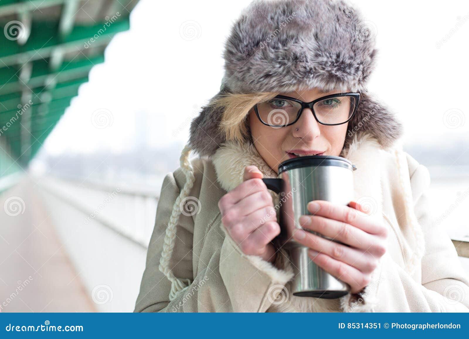 Portrait de café potable de femme de récipient isolé de boissons pendant l hiver