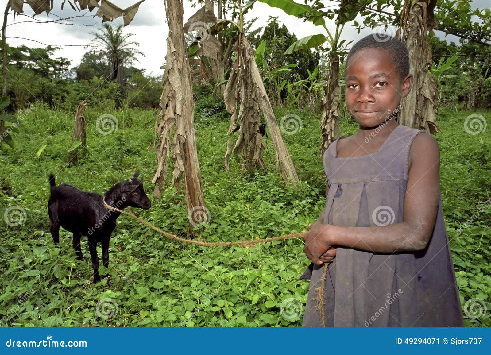 Portrait de chevrier ougandais de sourire avec la chèvre