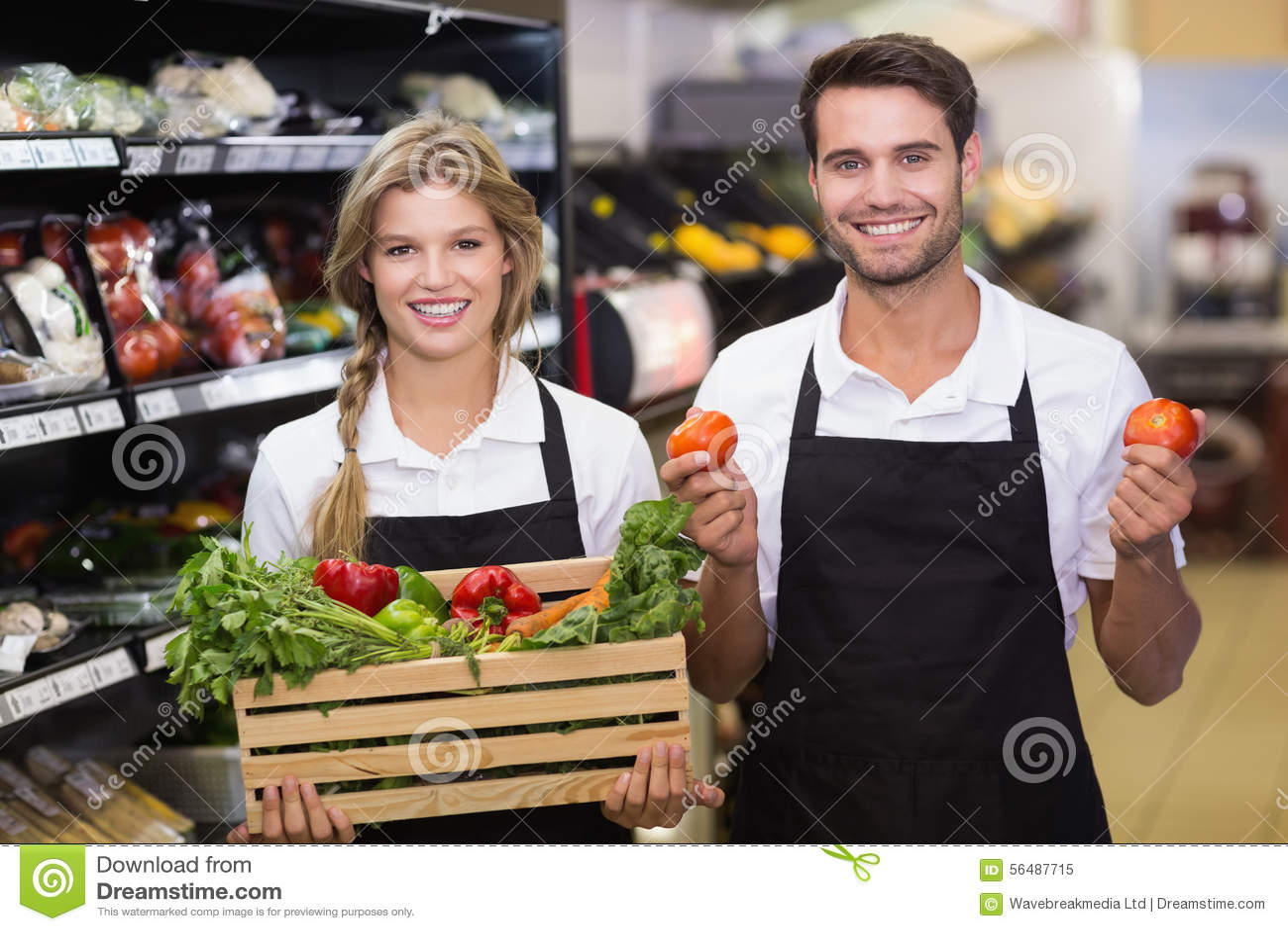 Portrait de collègues de sourire avec les légumes frais