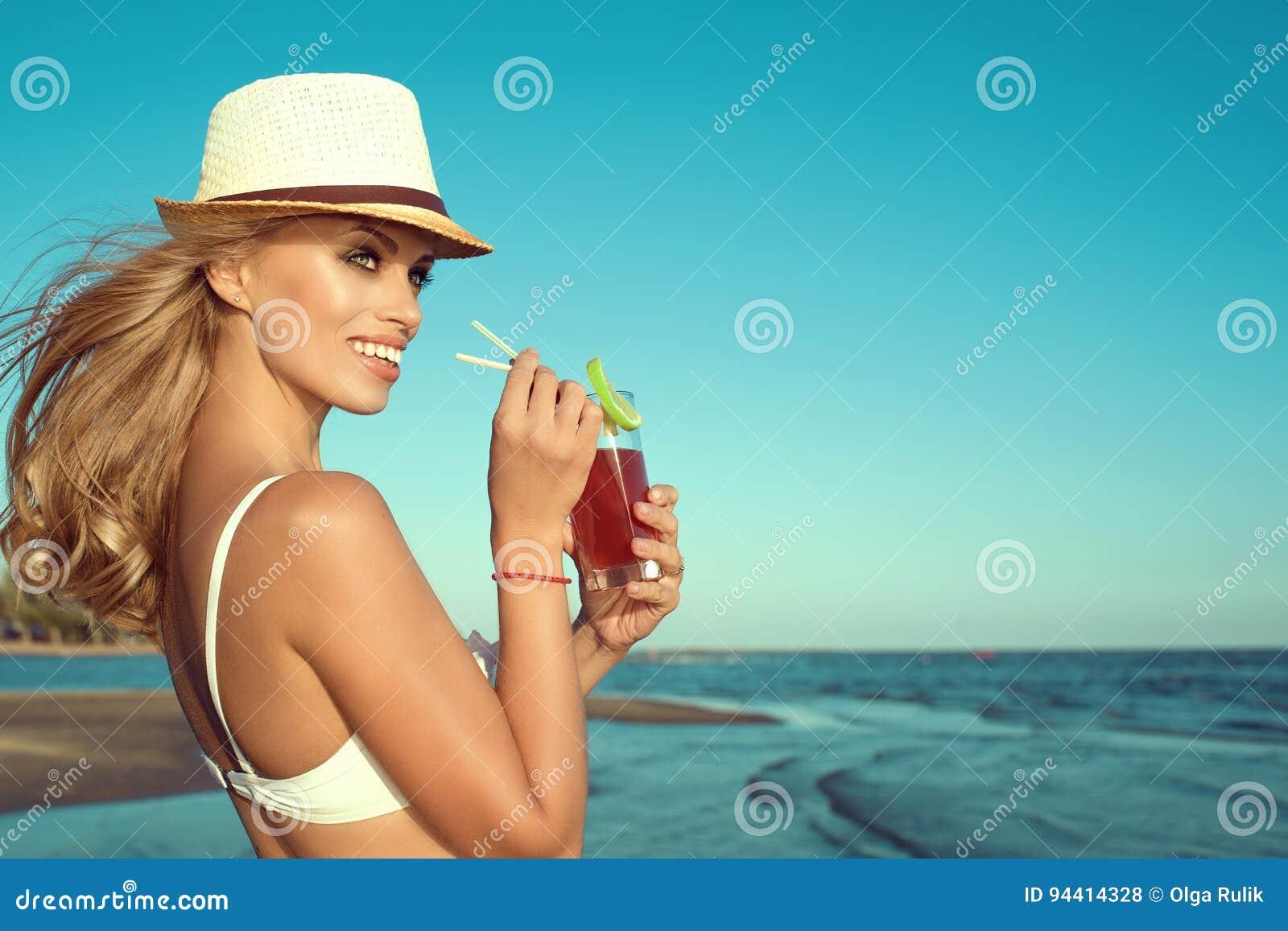 Portrait de dame blonde de sourire de jeune charme en soutien-gorge blanc de natation et cocktail potable du Panama par une paill