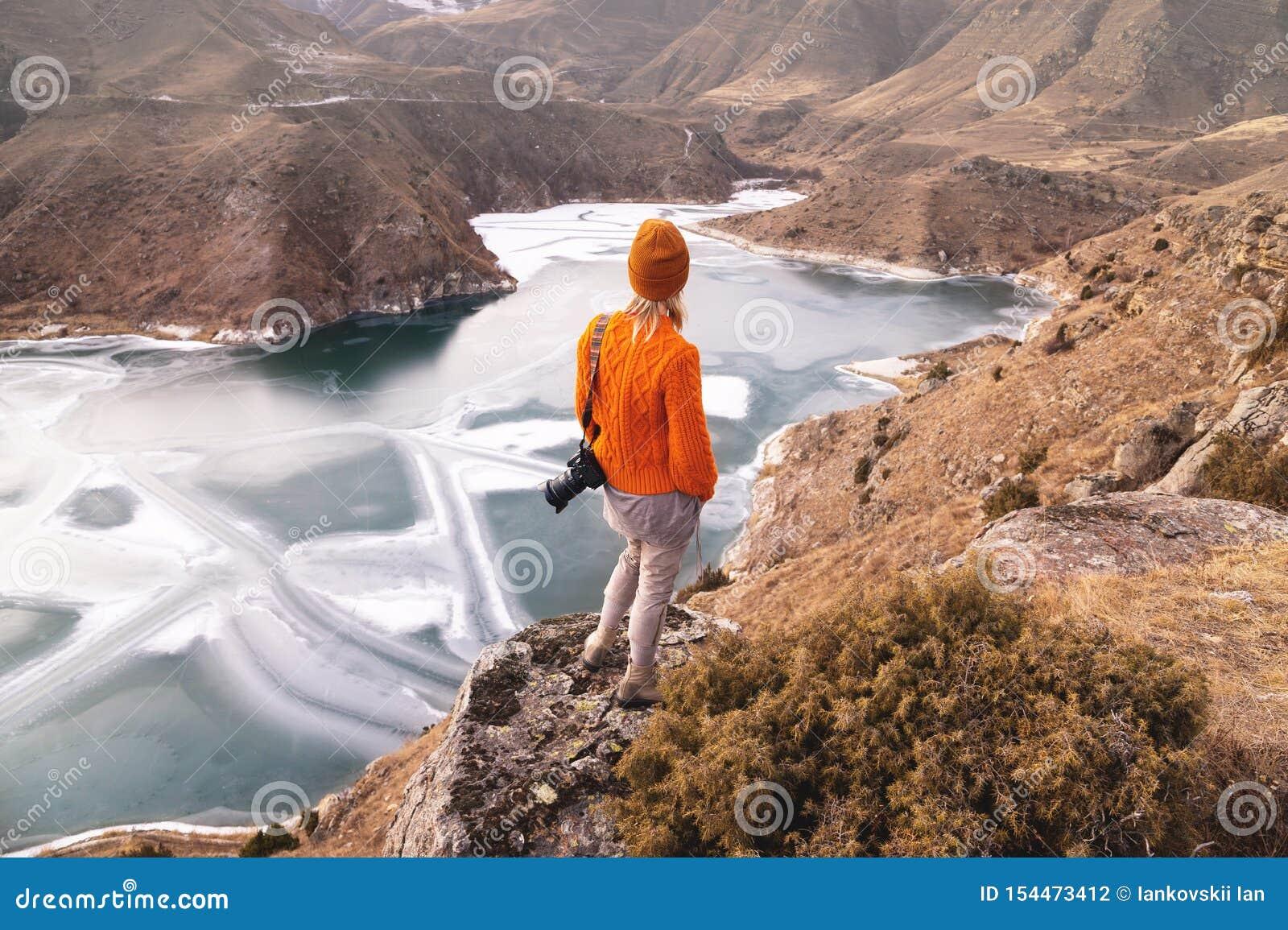 Portrait de derrière du photographe de voyageuse de fille dans un chandail et un chapeau oranges avec une caméra à disposition da