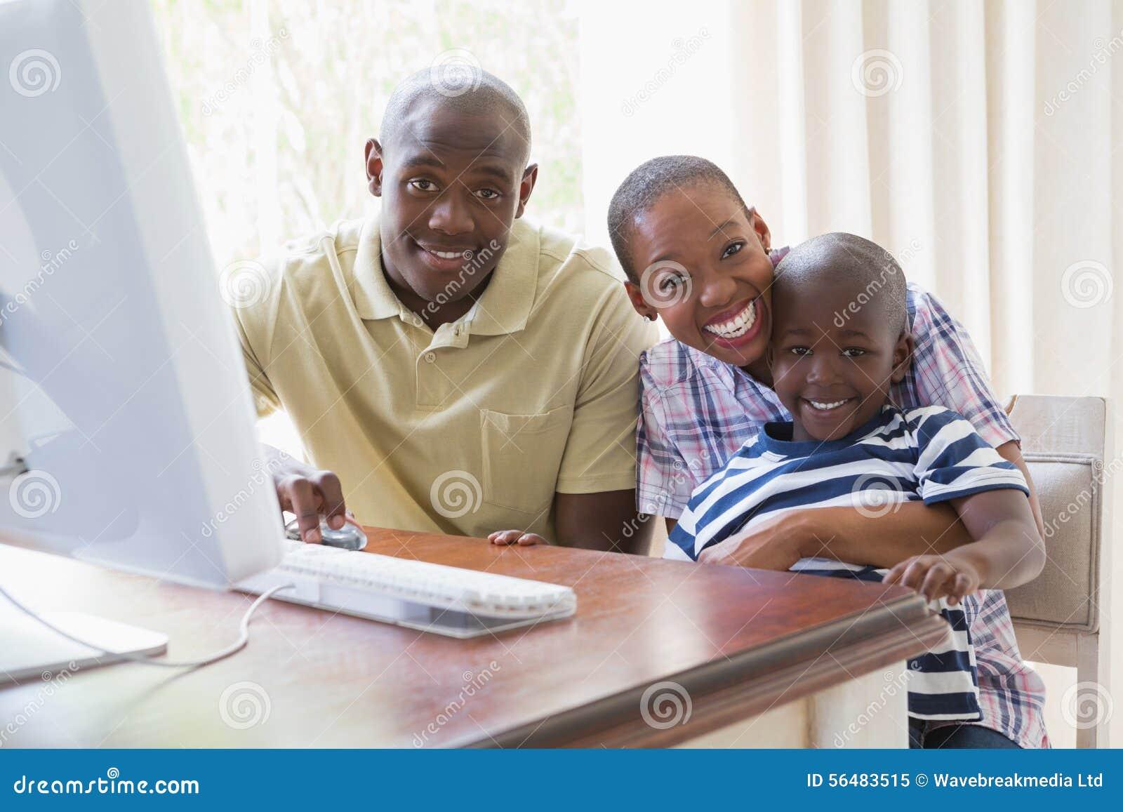 Portrait de famille de sourire heureuse utilisant l ordinateur