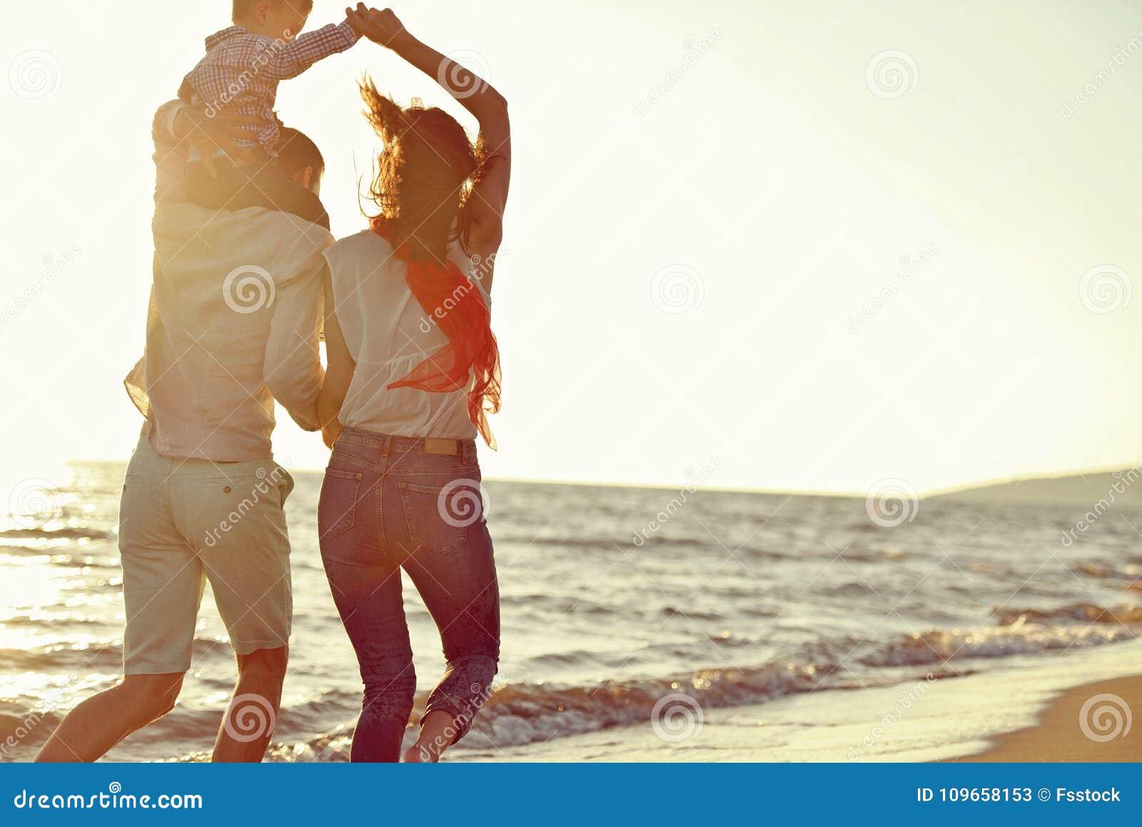 Portrait de famille heureuse et de bébé appréciant le coucher du soleil dans les loisirs d été