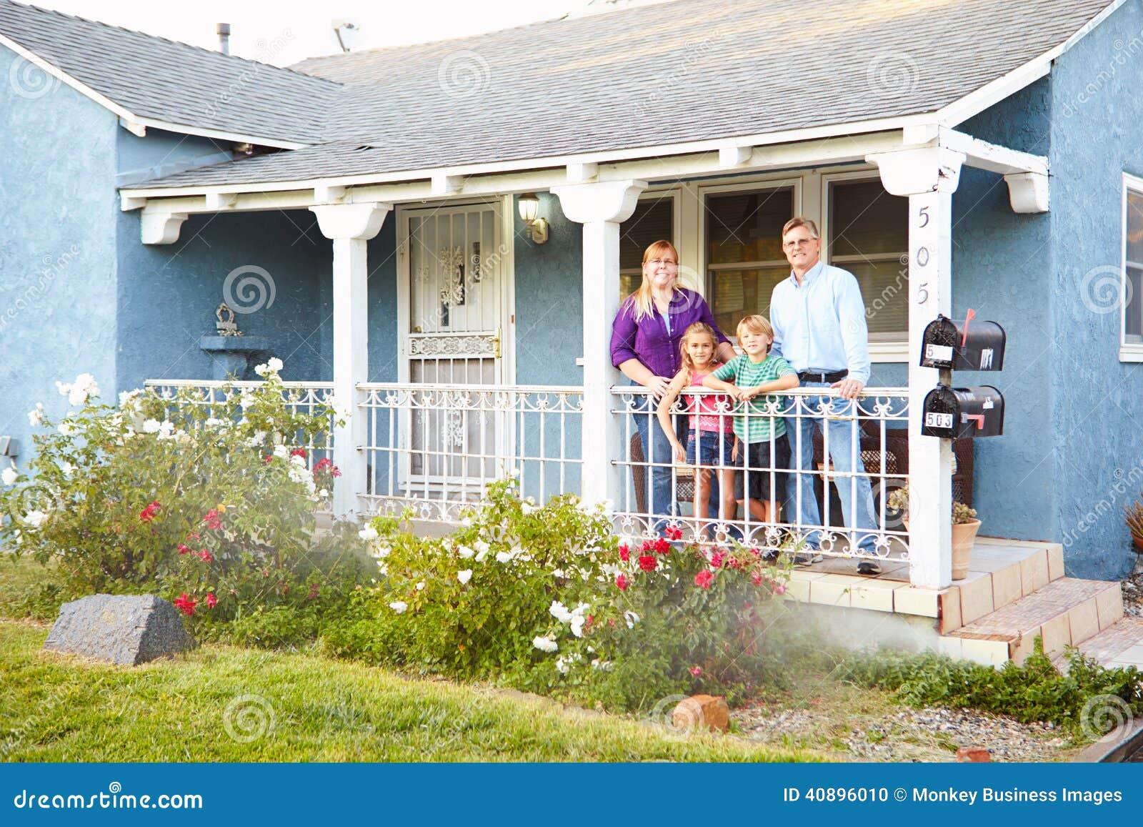 Le Porche De La Maison portrait de famille se tenant sur le porche de la maison suburbaine