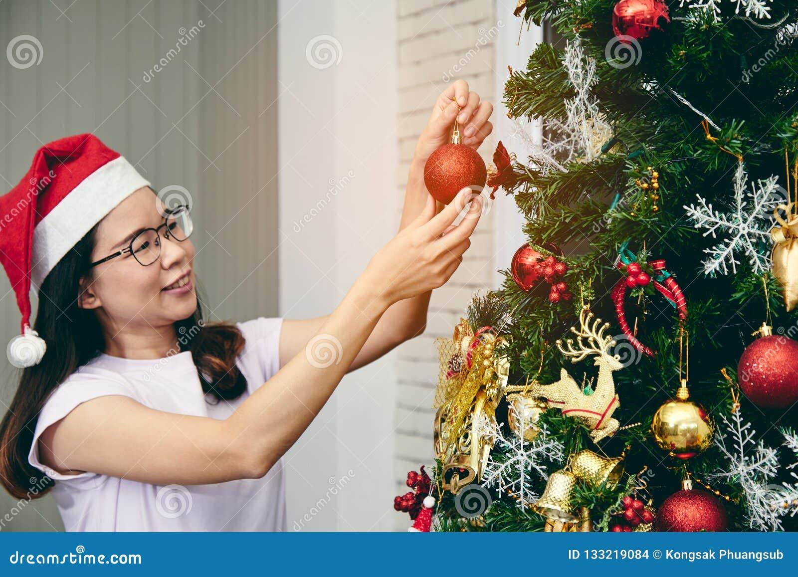 Portrait de femme asiatique utilisant le chapeau de Santa et décorant un arbre de Noël avec la boule rouge