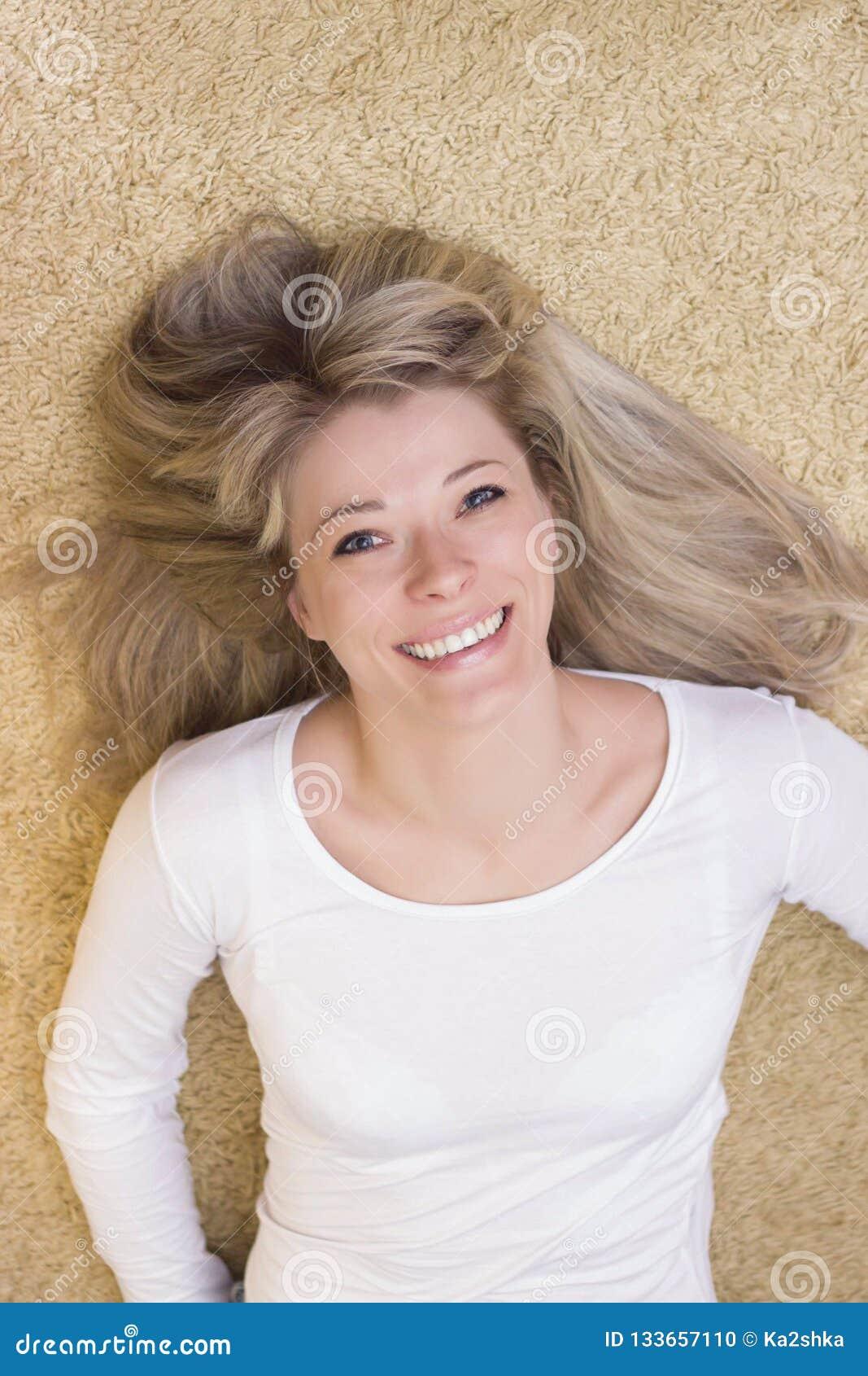 Portrait de femme se trouvant sur le plancher et le sourire