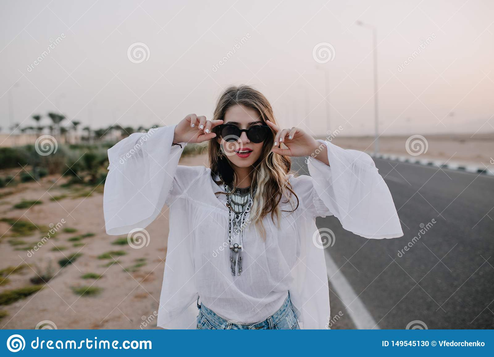 Portrait de fille ?l?gante gracieuse dans les lunettes de soleil noires et le chemisier blanc ayant l amusement ? c?t? de la rout