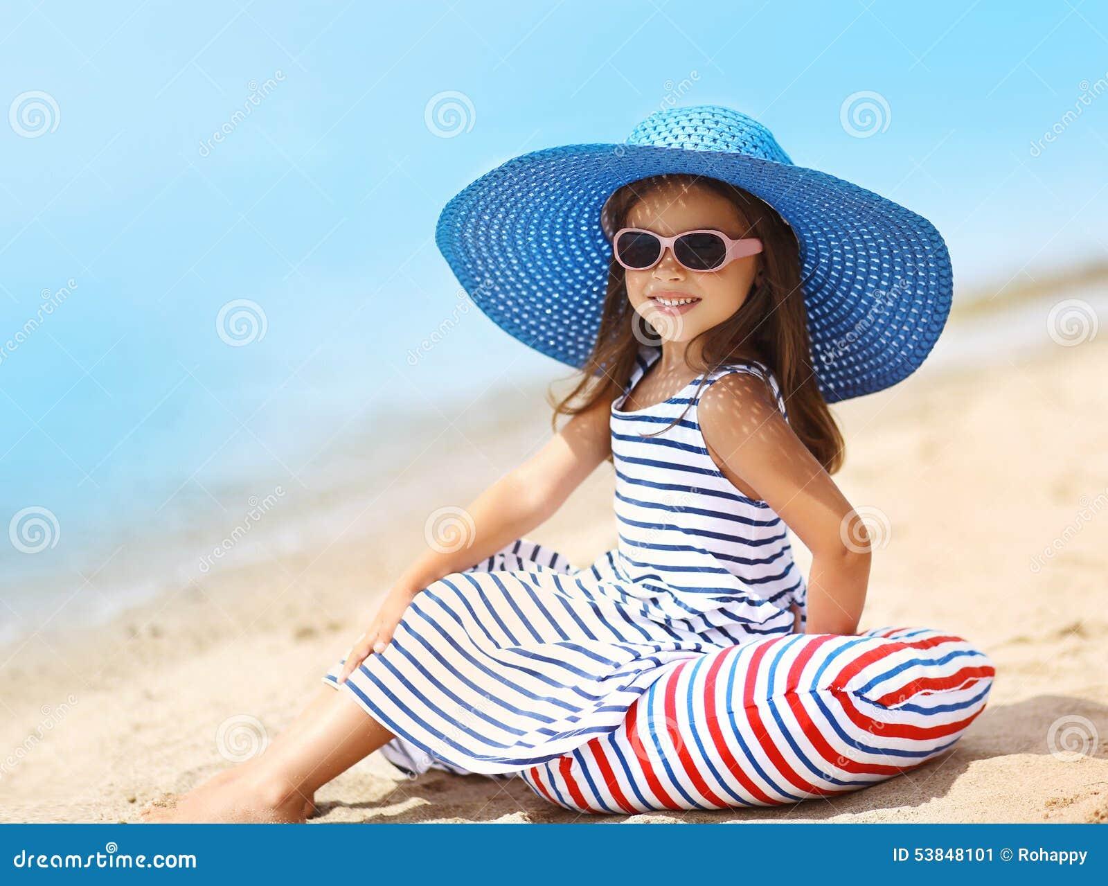 Portrait de fille assez petite dans une robe et un chapeau de paille rayés