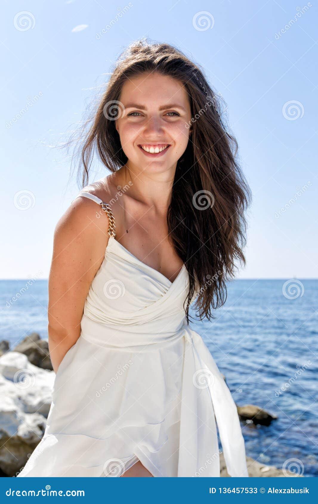Portrait de fille aux cheveux longs drôle dans la robe de mariage contre le bord de la mer