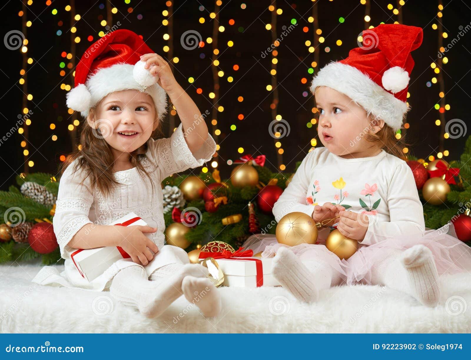 Portrait de fille d enfant en décoration de Noël, émotions heureuses, concept de vacances d hiver, fond foncé avec l illumination