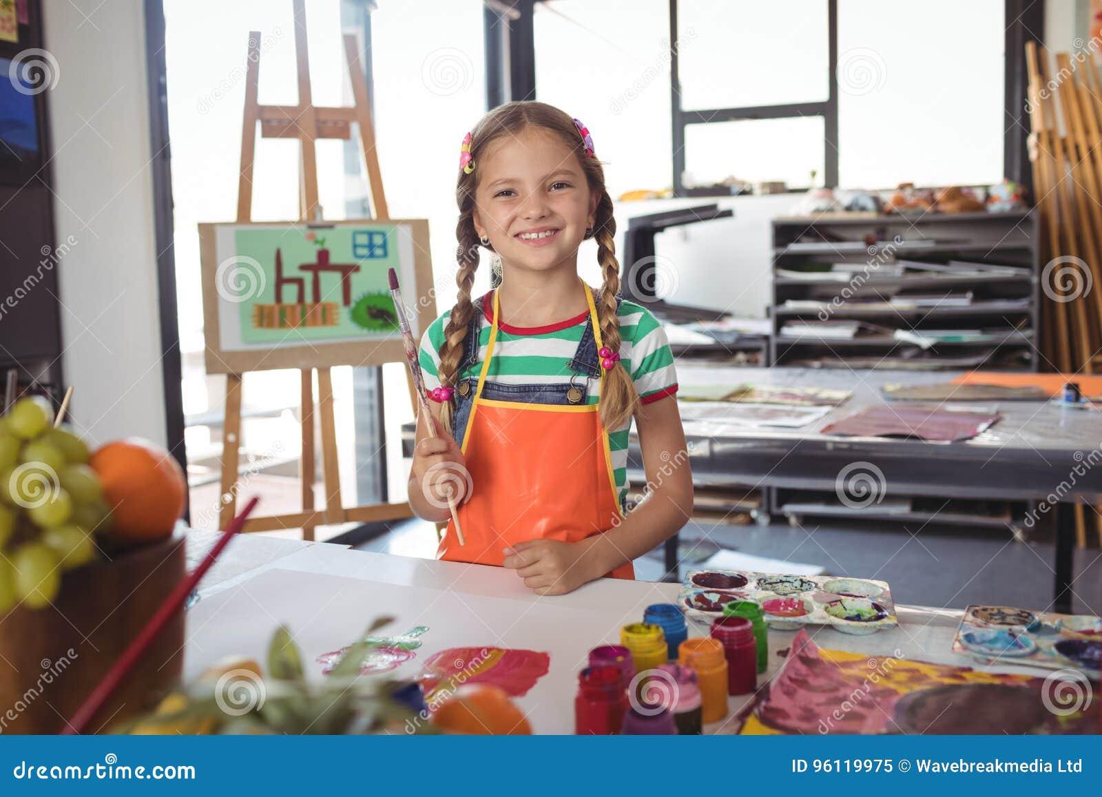 Portrait de fille heureuse tenant des pinceaux