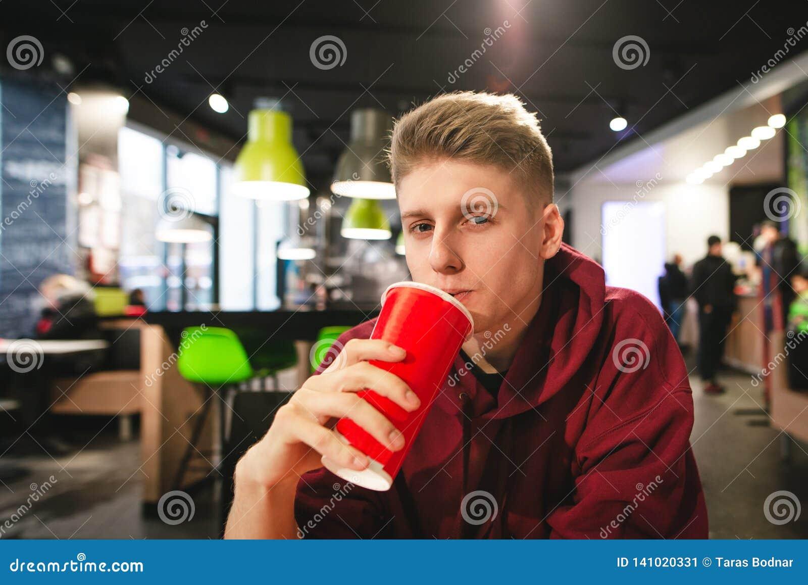 Portrait de garçon attirant avec un grand verre rouge dans sa main, buvant un enjeu et regardant la caméra