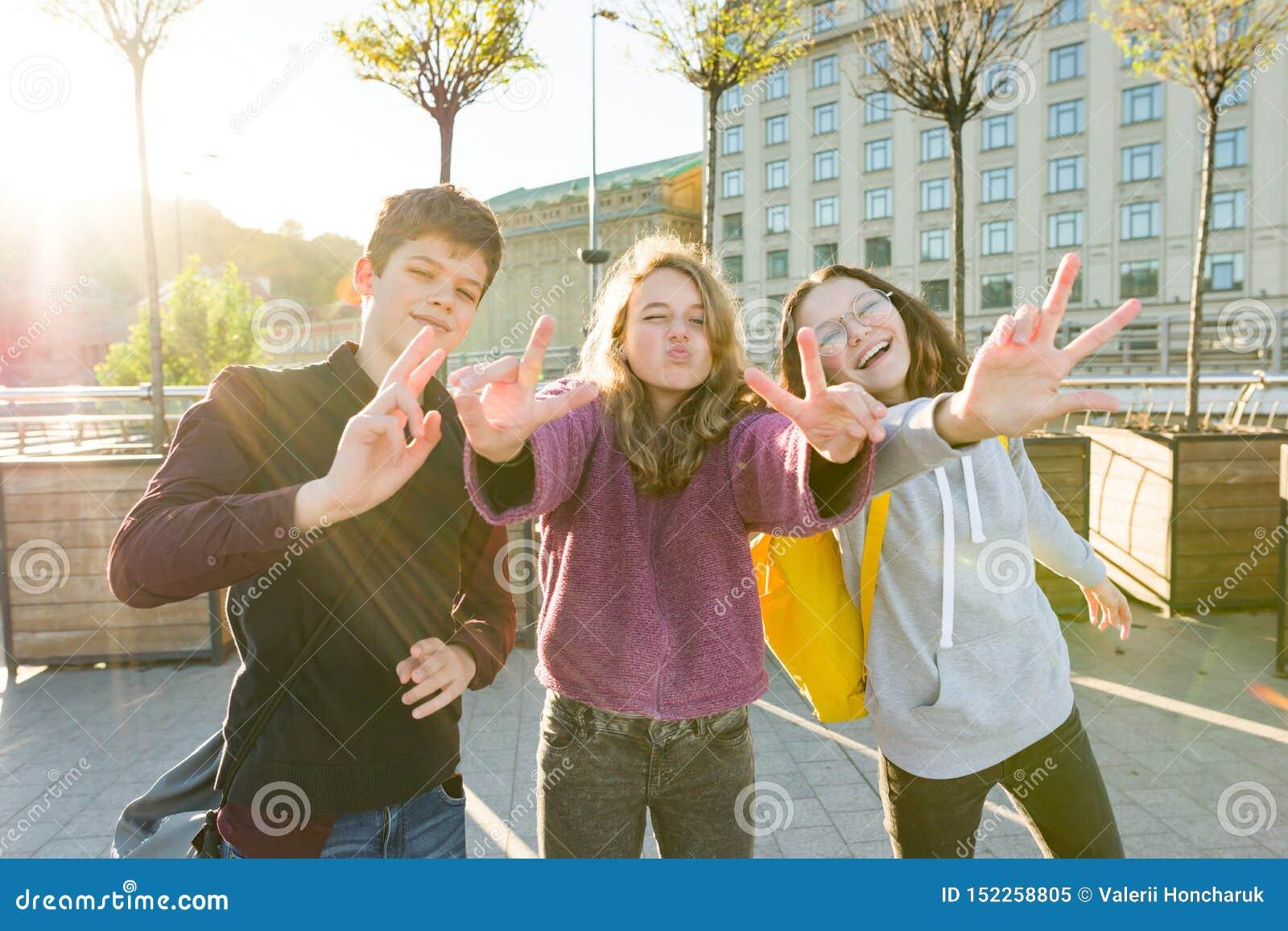 Portrait de gar?on de l adolescence d amis et deux de filles souriant, faisant les visages dr?les, montrant le signe de victoire