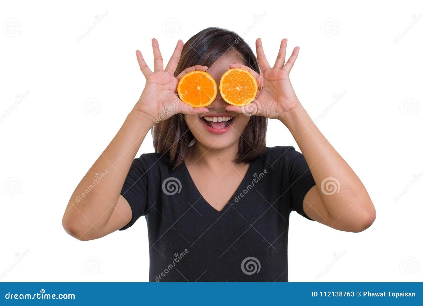 Portrait de jeune chemise asiatique de noir d usage de femme tenant les tranches oranges devant ses yeux et sourire d isolement s