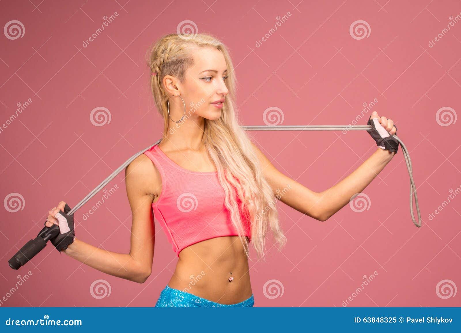 Portrait de jeune et en bonne santé blonde avec la corde à sauter