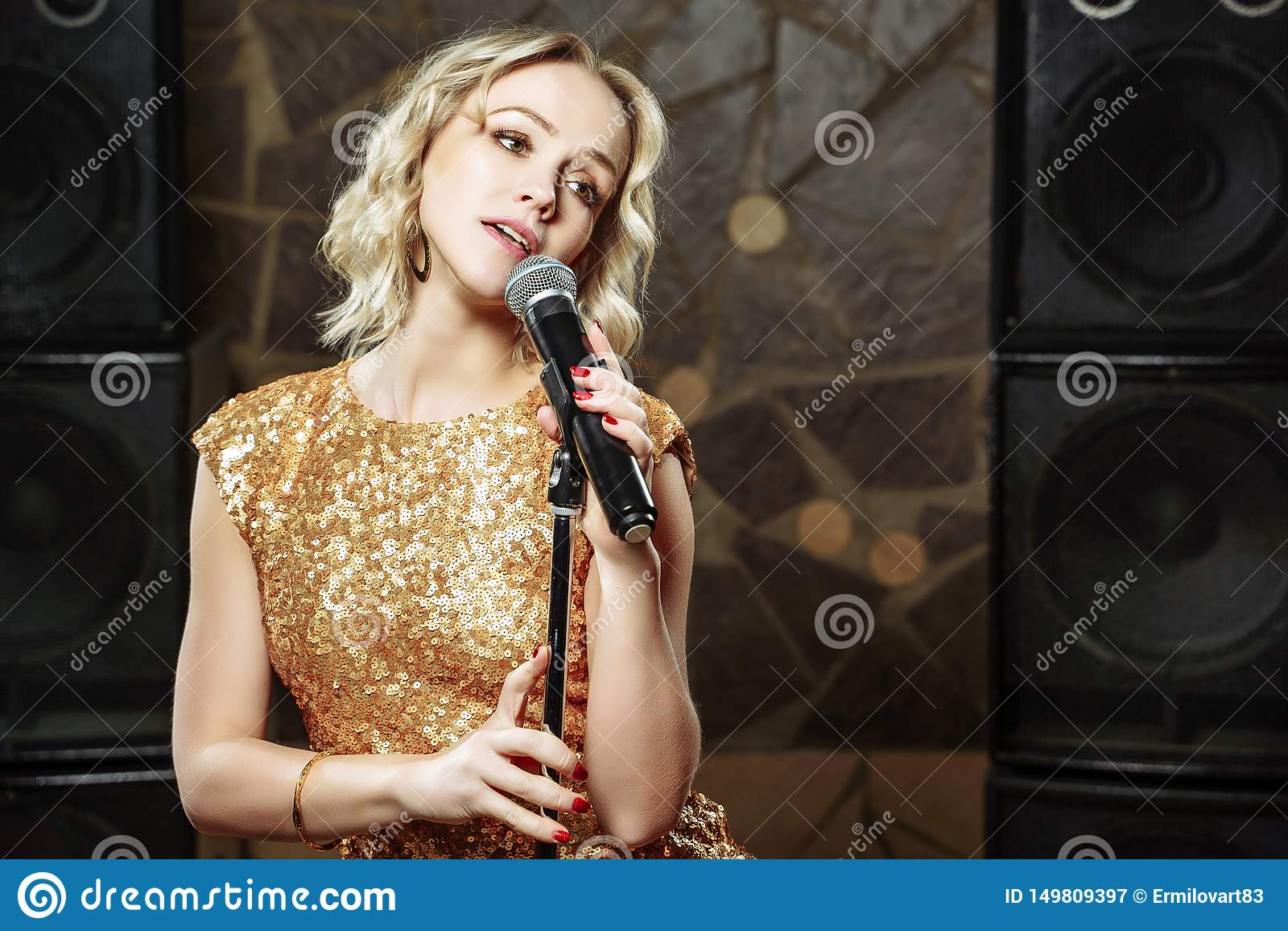 Portrait de jeune femme blonde avec le microphone sur le fond foncé