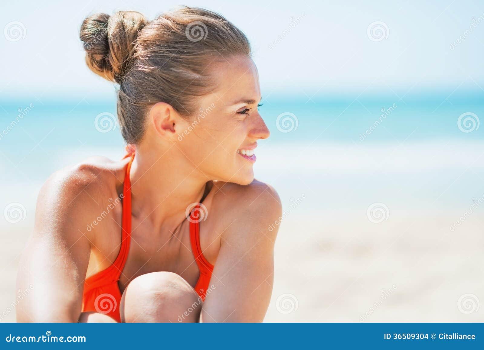 Portrait de jeune femme heureuse sur la plage regardant sur l espace de copie