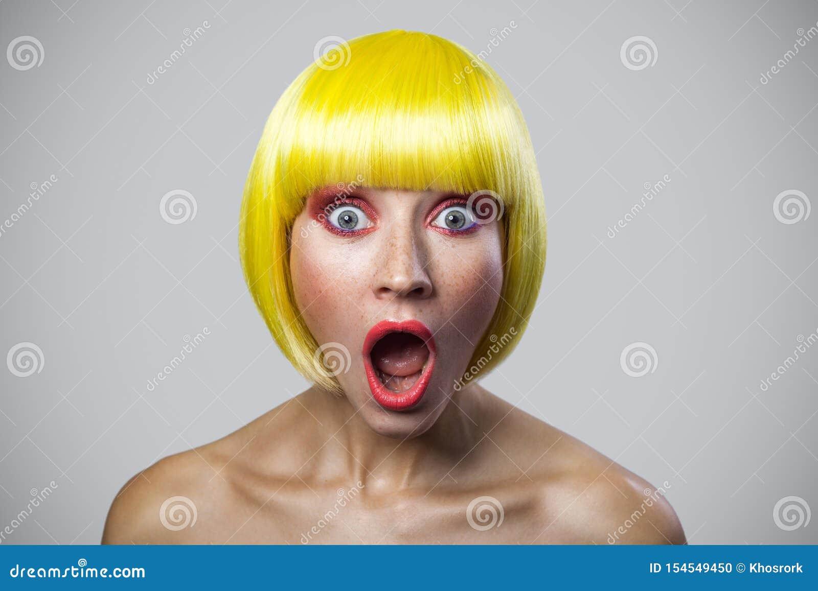 Portrait de jeune femme mignonne étonnée avec des taches de rousseur, maquillage rouge et perruque jaune, regardant la caméra ave