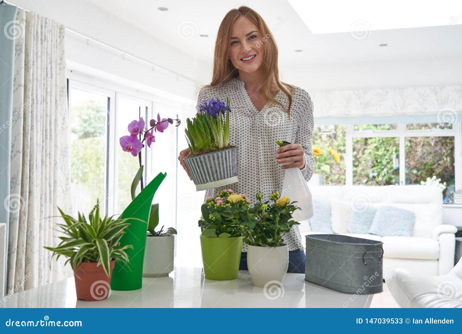 Portrait de jeune femme s inquiétant des plantes d intérieur à l intérieur