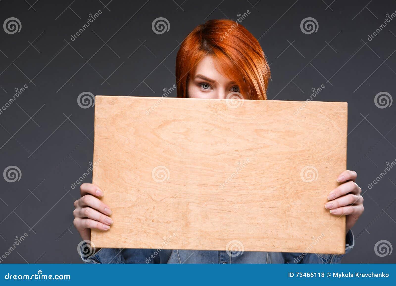 Portrait de jeune fille avec le bureau en bois au dessus du fond