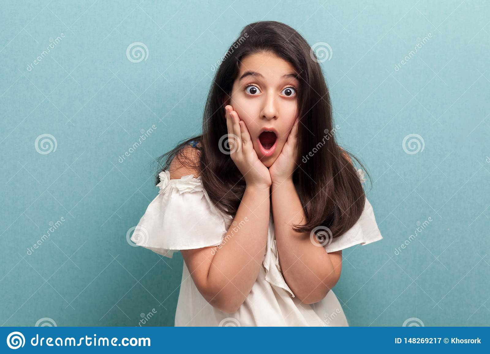 Portrait de jeune fille choquée de belle brune avec de longs cheveux droits noirs dans la position blanche de robe et de regarder