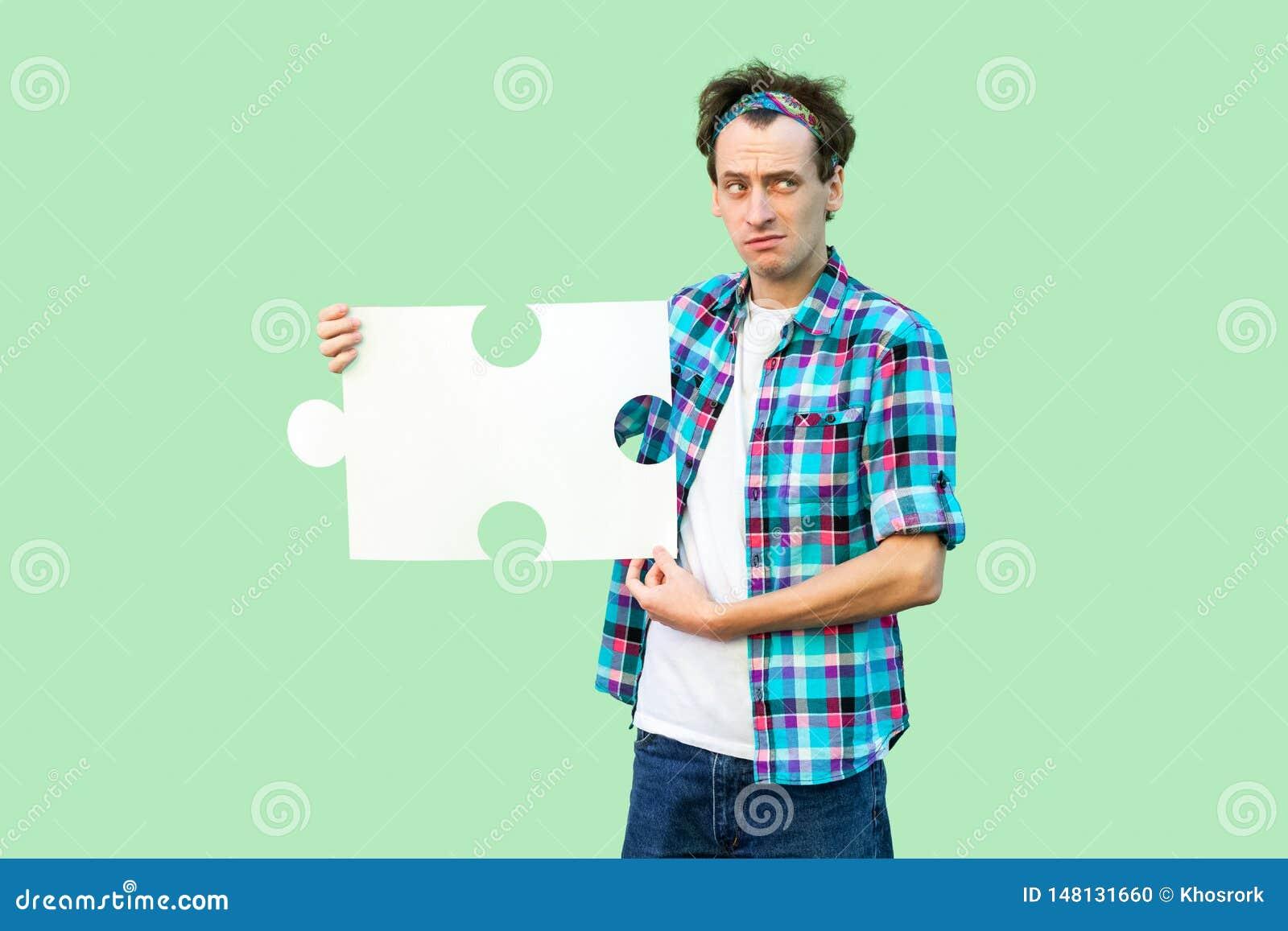 Portrait de jeune homme adulte de tristesse dans la chemise à carreaux tenant et tenant le grand morceau de puzzle, pensant à la