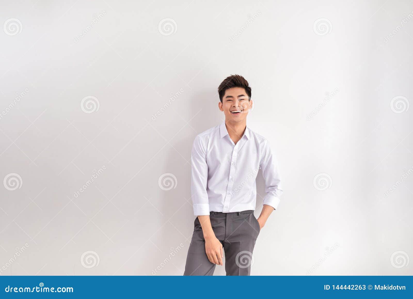 Portrait de jeune homme heureux se tenant sur le fond blanc