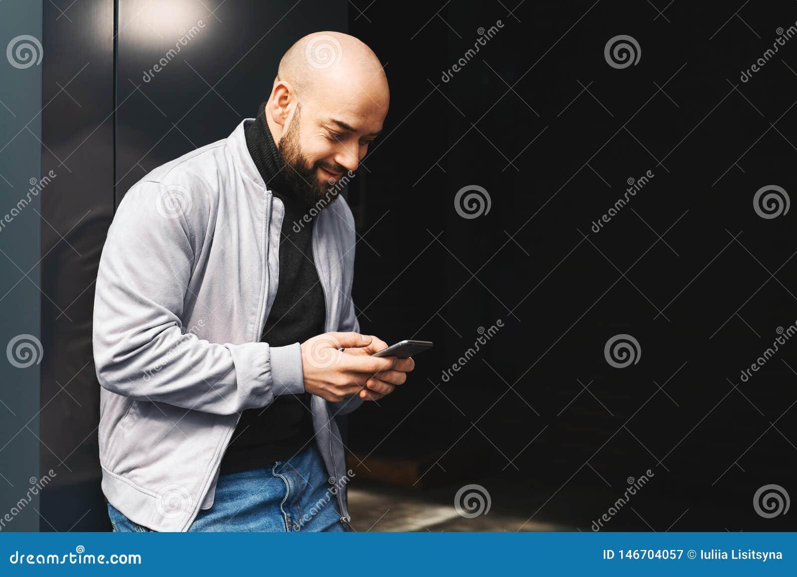 Portrait de jeune homme de sourire utilisant le smartphone sur la rue de ville L homme envoie le message textuel lifestyle R?seau