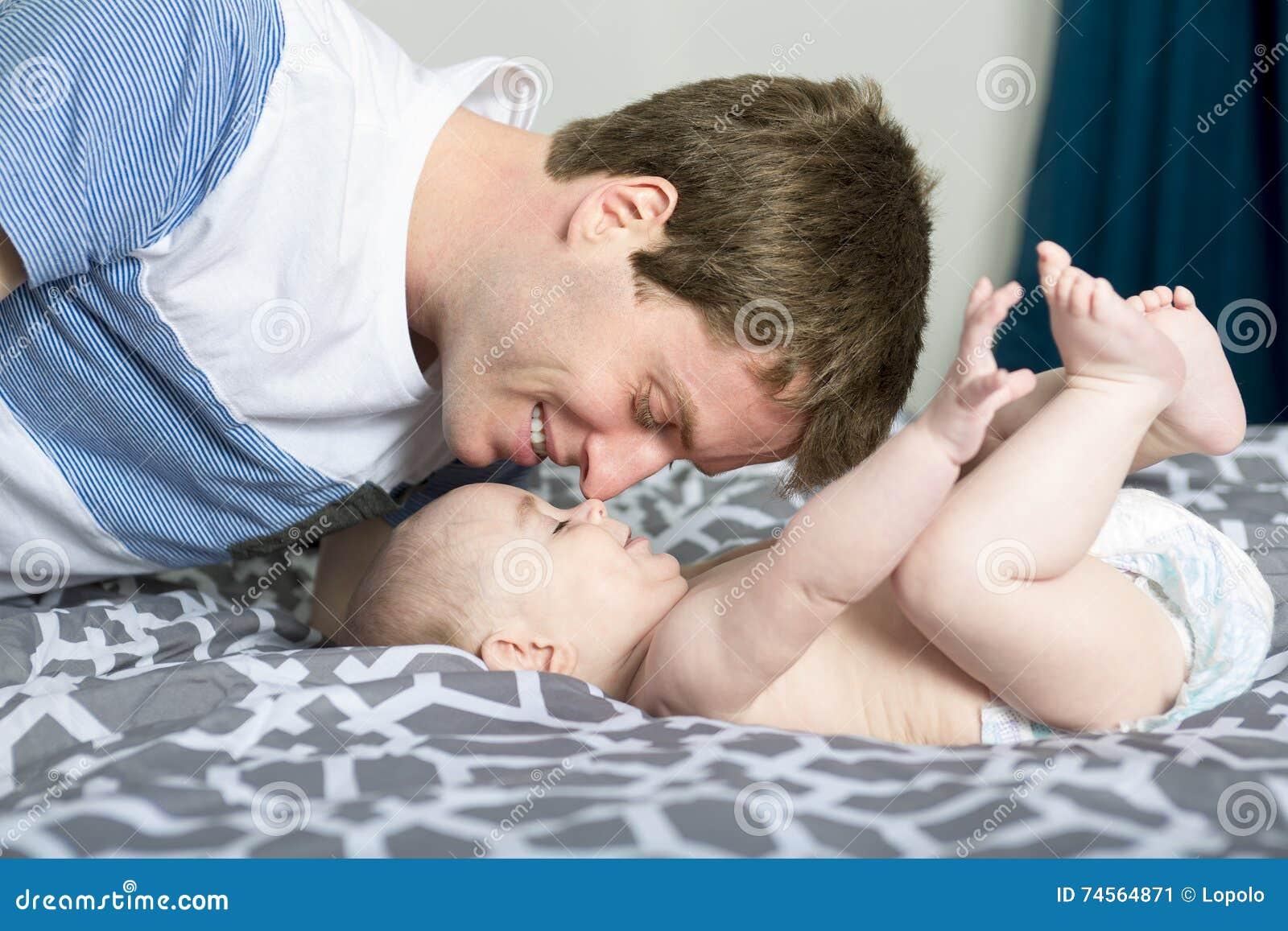 Portrait de jeune père heureux avec un bébé dans le lit à la maison