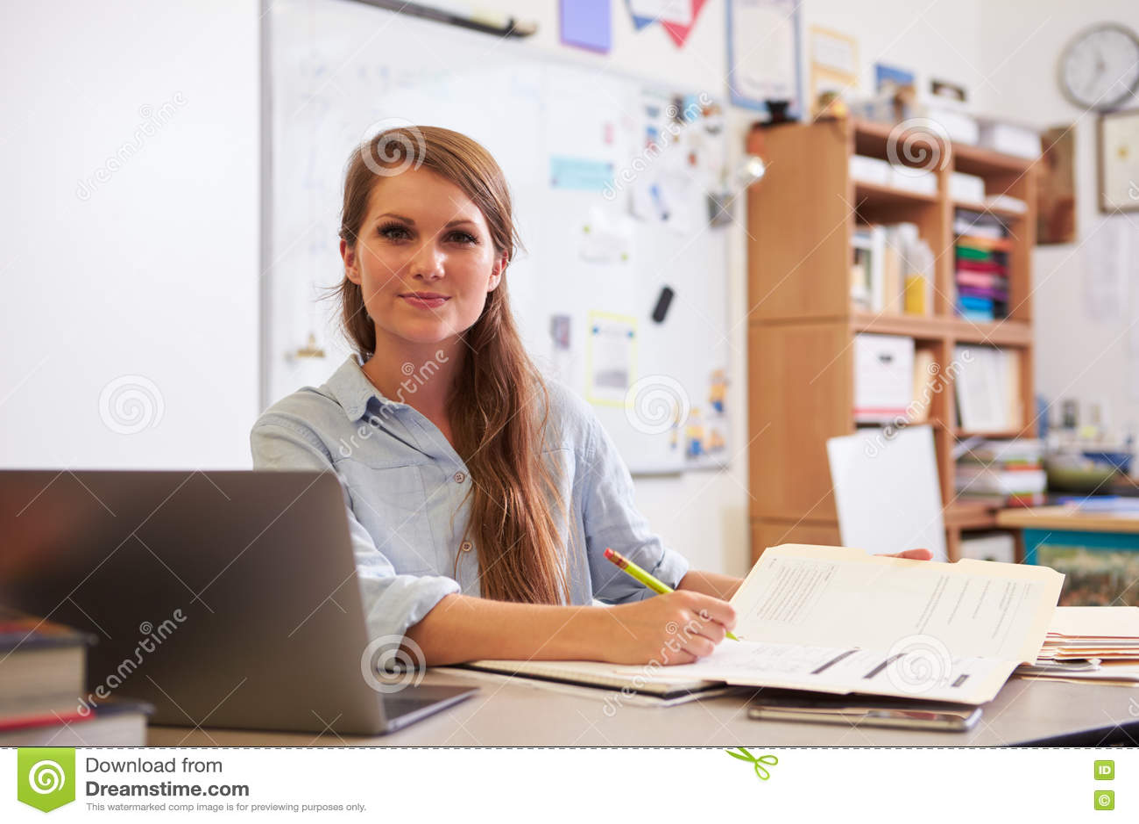 Portrait de jeune professeur féminin au bureau regardant à l appareil-photo