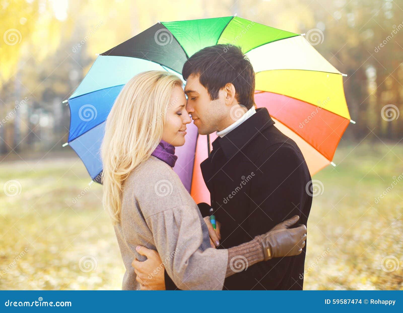 Portrait de jeunes ajouter affectueux au parapluie coloré étreignant l automne